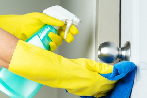 Cleaning door knob with alcohol spray for Covid-19 Coronavirus prevention