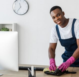 Selective focus of smiling african american cleaner cleaning telephone with rag on office table